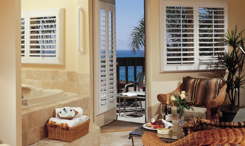 Plantation shutters on casement windows in a beachfront house.