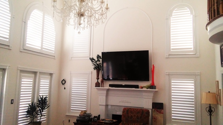 Tampa great room with wall-mounted TV and arched windows.