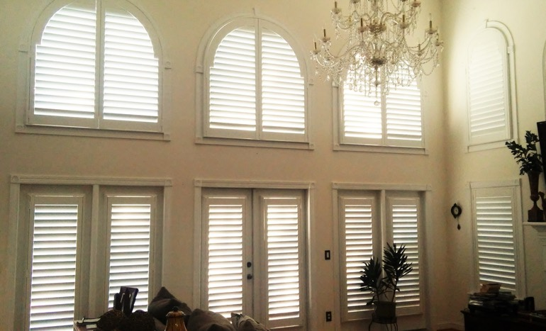 Family room in open concept Tampa home with plantation shutters on arch windows.