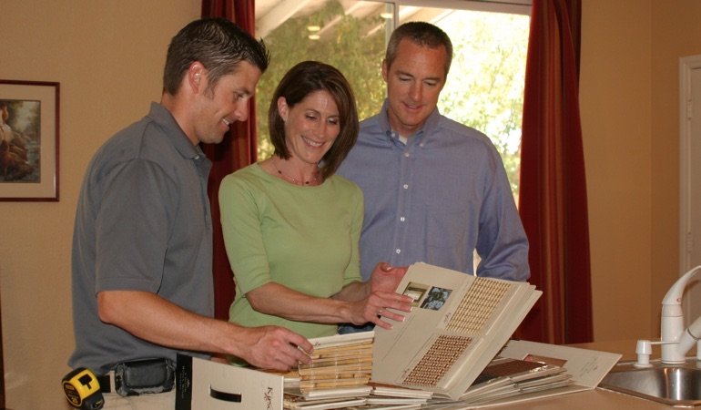 Homeowners choosing between window treatment samples.