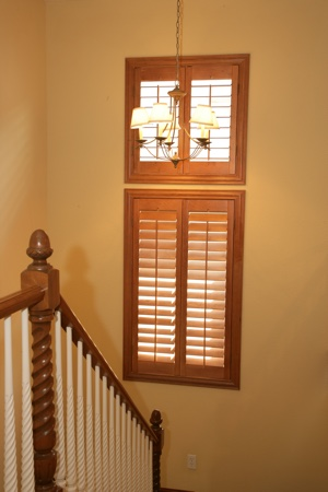 Wooden plantation shutters in tan stairwell.