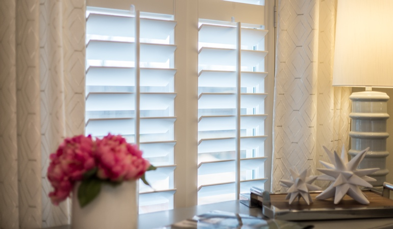 Plantation shutters by flowers in Tampa