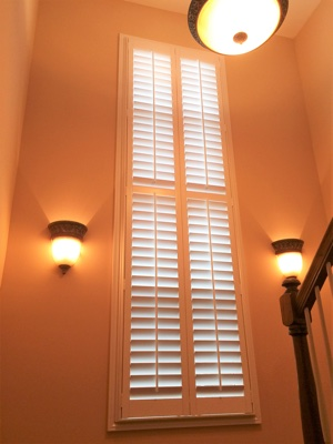 White plantation shutters in well-lit stairwell.