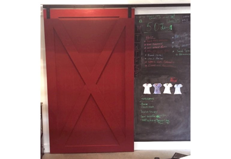 Red sliding barn door with black track next to chalkboard