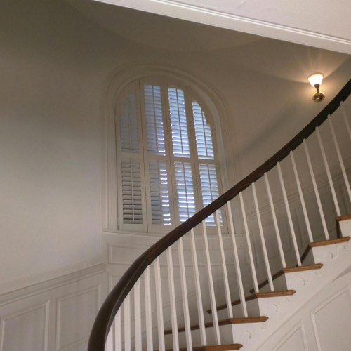White plantation shutters adorning arched window located in curved stairwell.