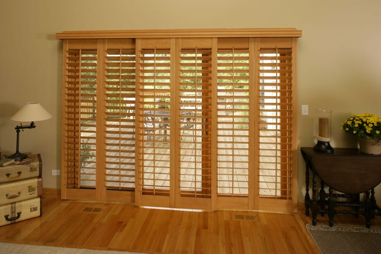 plantation shutters on sliding door connecting to back porch.