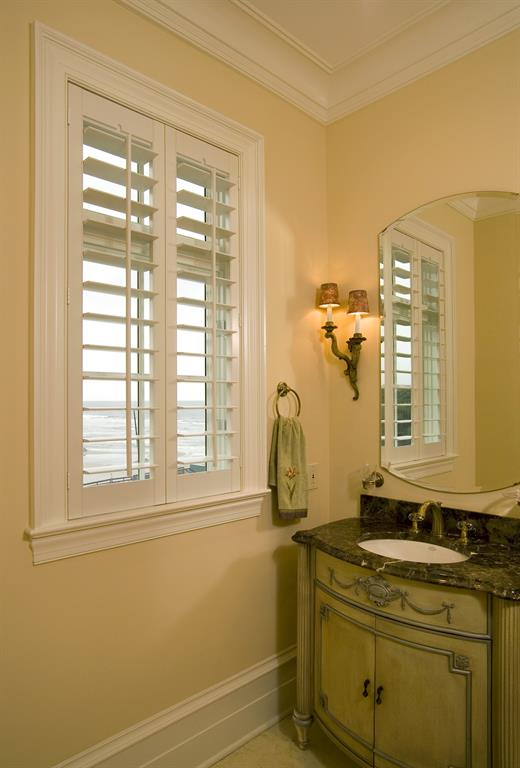 White shutters in a bathroom give a view of the ocean