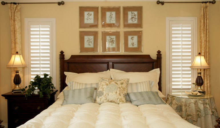 Beige bedroom with white plantation shutters covering windows in Tampa