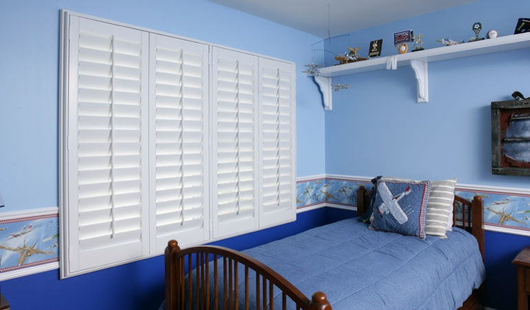 Blue kids bedroom with white plantation shutters in Tampa