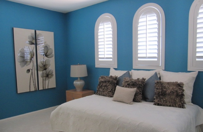 White arched plantation shutters in blue bedroom