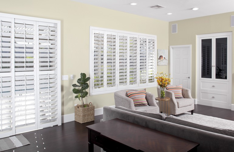 Living room with dark wood floors and white plantation shutters
